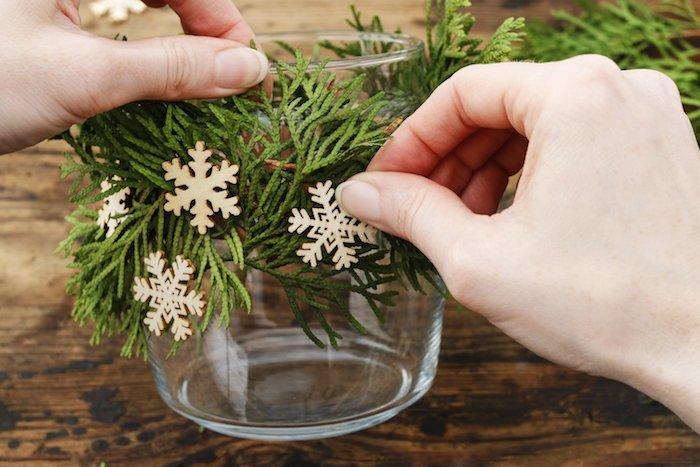 exemple bougeoir de noel à fabriquer en verre décoré de branches de pin et flacons de neige en bois artificiels