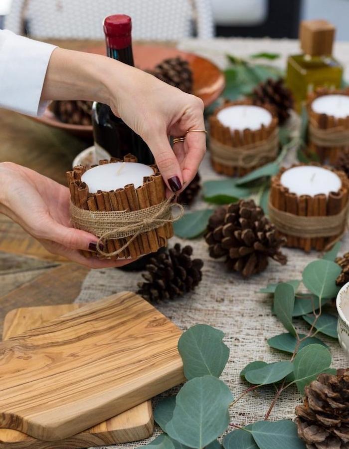 décoration de noel à fabriquer pour adultes, bougeoir en bâtons de cannelle noués d une ficelle et bande de jute, composition décorative avec branches et pommes de pin
