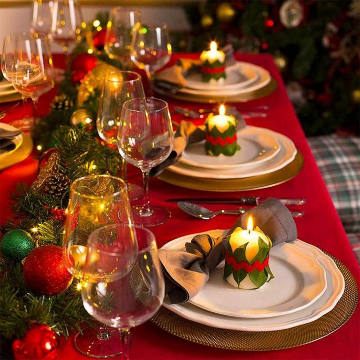 bougie envelopp e de feuilles vertes couronne de brins de pin avec des boules d coratives jaunes et rouges verres  vin nappe rouge