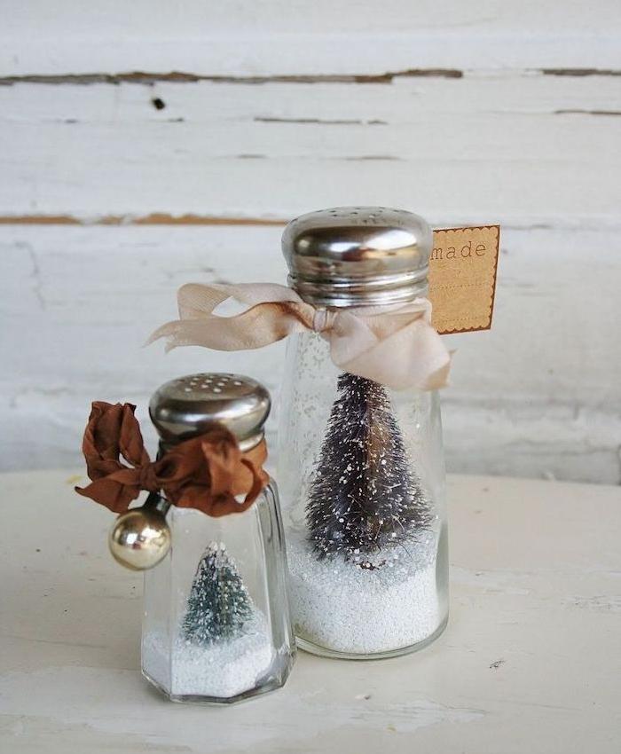 salière recyclée pour faire une boule à neige avec neige artificielle, figurine de sapin et ruban rose et marron, deco noel fait main
