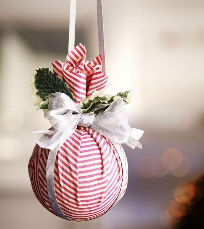 deco boule de noel originale enveloppée de tissu rouge et blanc à rayures, ruban blanc en noeud et decoration de feuilles