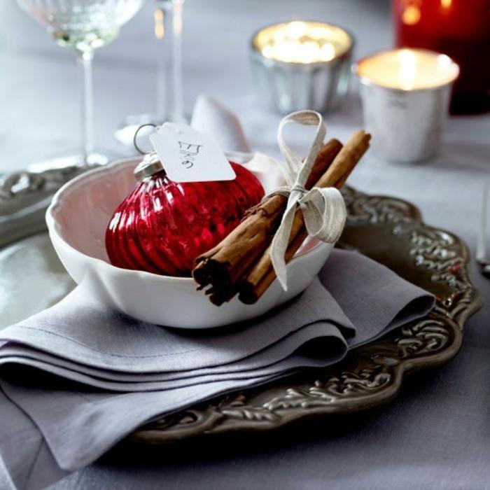 boule de noel rouge assiette blanche plateau de service en argent b tons de cannelle serviette tissu gris porte bougies argent s