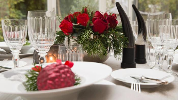 boule de noel rouge pos e dans une assiette blanche centre de table roses rouges dans un vase rond verres en cristal deco table noel a fabriquer