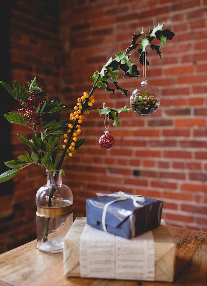 idee de decoration de table de noel a faire soi meme, vase en verre avec branches de houx et boules de noel transparentes remplies de houx