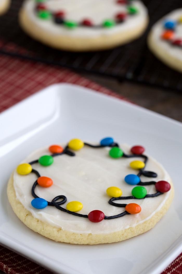 sable de noel facile et rapide, cookies ronds avec glaçage royal et mini bonbons en forme guirlande lumineuse de noel