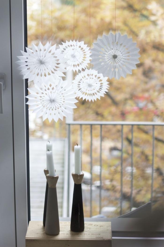 des flocons de neige en papier en forme de rosaces suspendues à la fenêtre, suspensions de noël en papier à fabriquer deco noel