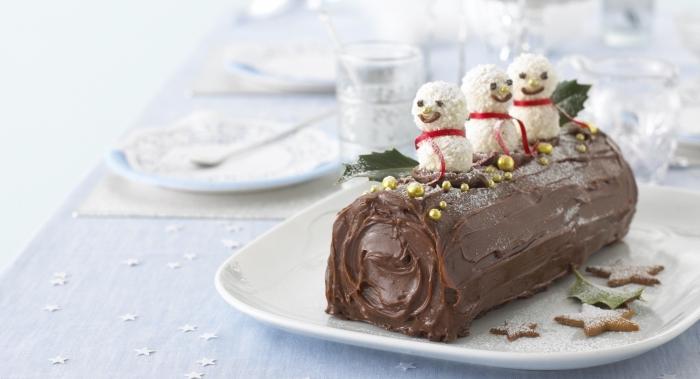 une buche de noel facile et rapide à la crème au mascarpone et au glaçage chocolat, décoré avec trois bonhommes de neuge et quelques feuilles de houx artificielles, déco de table de noël toute blanche et étoilée