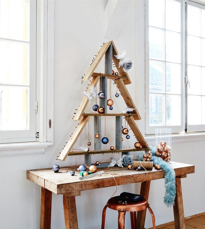 sapin en bois fait avec des morceaux de palettes, boules de noel décoratives oranges et bleues, tabouret finition cuivrée, guirlande bleue