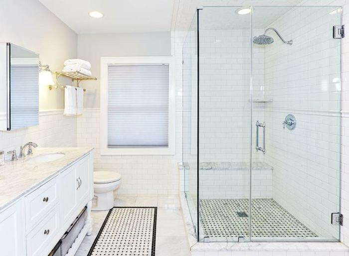 salle de bain toute blanche, petites tuiles noires, porte serviette dorée, carreaux métro blancs, banquette blanche, meuble sous vasque blanc, mitigeurs chromés