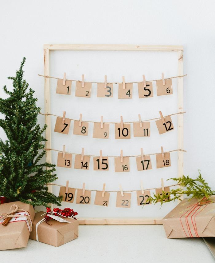 cadre bois clair avec des étiquettes papier kraft avec chiffres noirs suspendus sur des fils à des pinces à linge bois, mini sapin de noel décoratif et paquets cadeau
