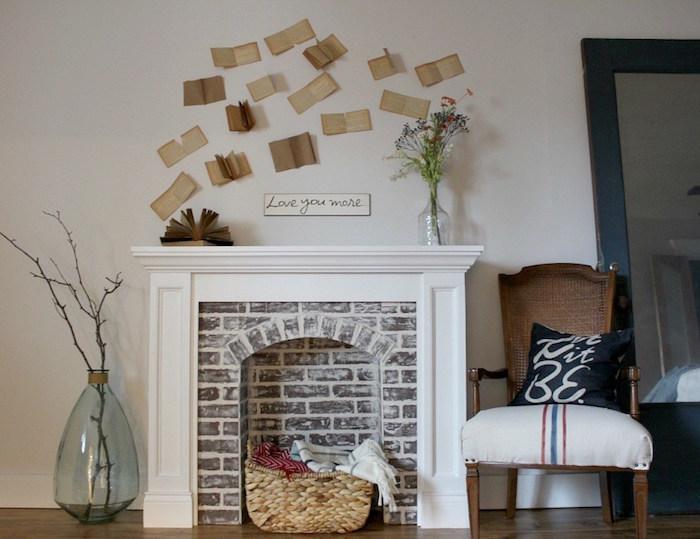 fausse cheminée déco avec manteau imitation briques avec panier deco dans foyer avec mur blanc et pages de livres anciens collées sur le mur
