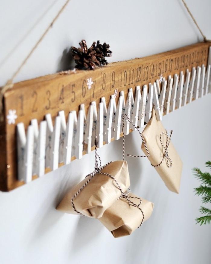 planche de bois brut avec des pinces à linge bois blanchies et petits paquets papier krafr suspendus, decoration murale de noel calendrier de l avent rustique