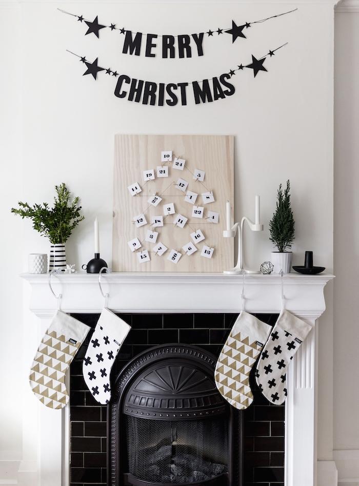 panneau bois clair avec des étiquettes blancs numérotés arrangés sous la forme d un sapin de noel, déco cheminée noir et blanc, accents mini sapin vert