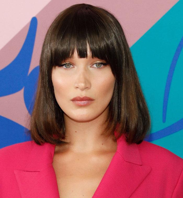 carré long avec frange style coiffure vintage femme brune aux yeux verts et veste retro rose