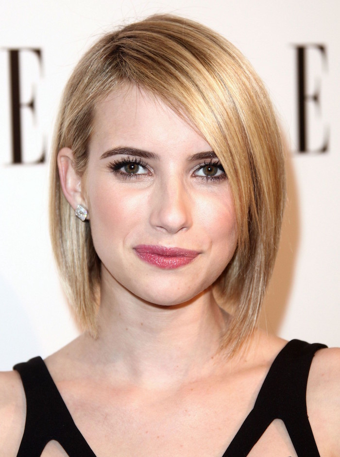 femme blond avec coupe au carré asymétrique avec frange tombant sur cote du front et robe noire