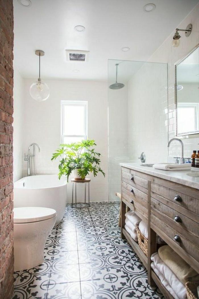 salle de bain au sol carreaux de ciment, meuble en bois, tiroirs et rangement de serviettes, tabouret, plante verte, murs peints blancs, mur en briques