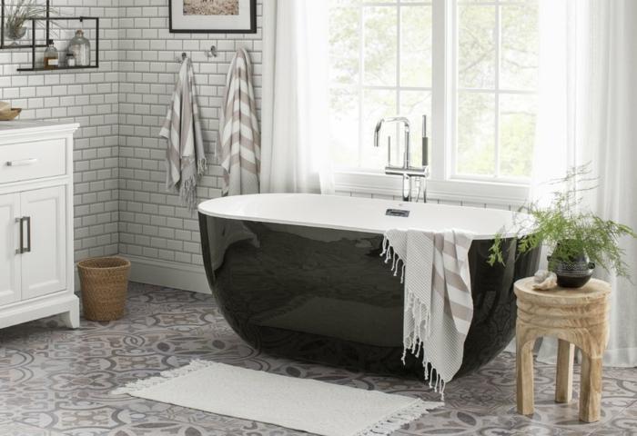 sol en carreaux de ciment, baignoire noire, petit tabouret en bois naturel, carreaux blancs, fenêtre aux rideaux blancs