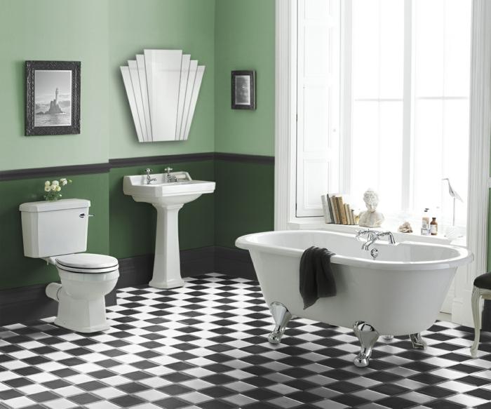 salle de bain simple au carrelage damier, baignoire blanche, miroir décoratif, grande fenêtre, statuette blanche, livres au rebord de la fenêtre