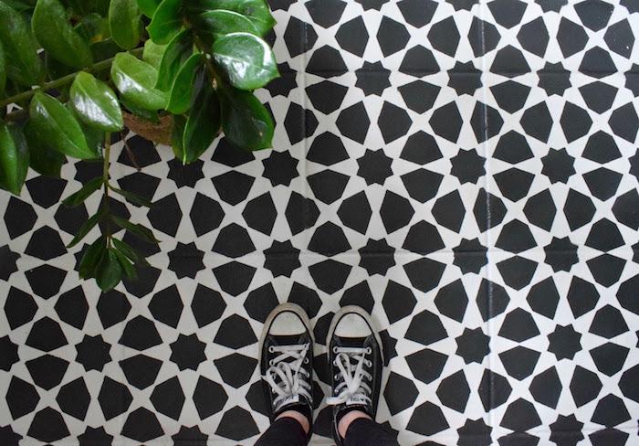 peindre du carrelage avec motif original en pochoir noir sur blanc sur sol de maison