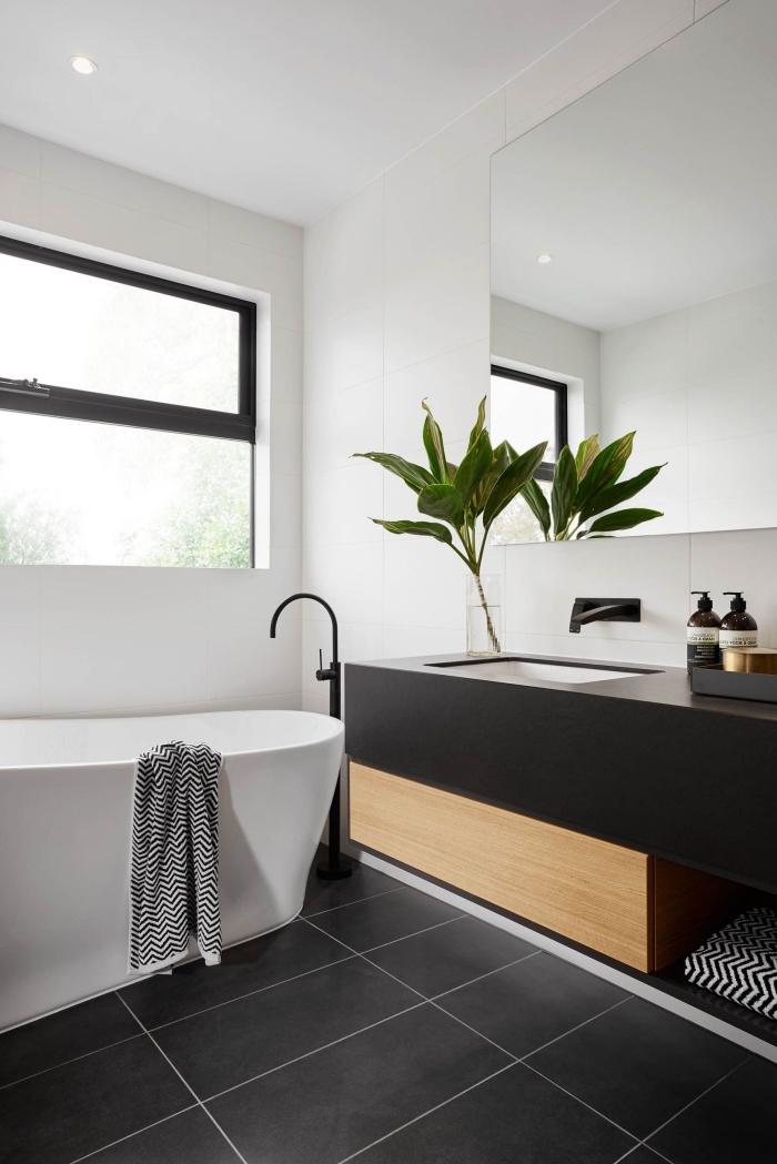 design stylé dans une salle de bain moderne aux murs blancs avec carrelage de sol en noir et meuble sous vasque en noir et bois