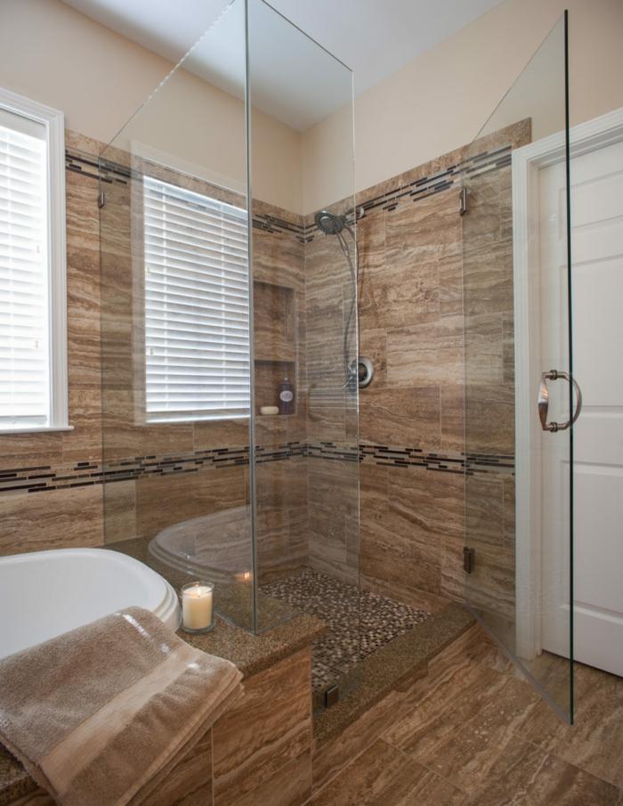 salle de bain travertin, paroi en verre, sol mosaique, bougie allumée, cloisons en verre, fenêtres avec rideaux blancs, porte blanche, salle de bain en beige et blanc