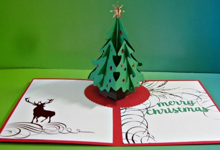 réalisation carte de Noel, exemple d'activité manuelle avec papier, modèle de carte avec sapin pop up décoré en strass coloré et étoile scrapbooking dorée