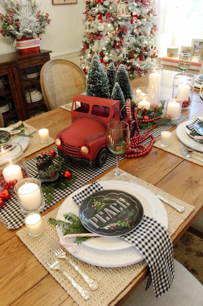 centre de table camion vintage rouge portant des sapins boules de noel et feuilles dispers es table en bois bougies blanches chemin de tabme carr  e1541169419621