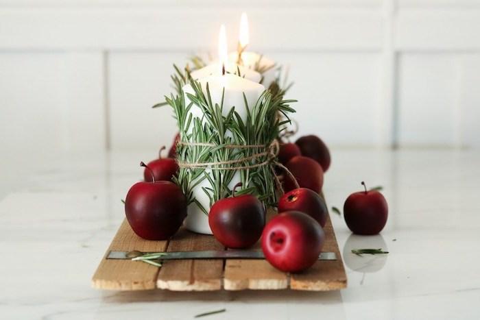 idee originale deco centre de table noel en planches bois rustique avec bougies enveloppées de romarin et deco de pommes de pin rouges, centre de table noël fait maison