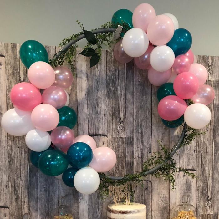 ballons attachés à un cerceau, déco avec feuillage, cloison en bois, deux groupes de ballons multicolores