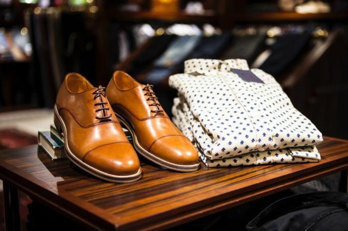 codes vestimentaires pour l'homme moderne, chemises pliées à sapins, chaussures camel, table en bois laqué