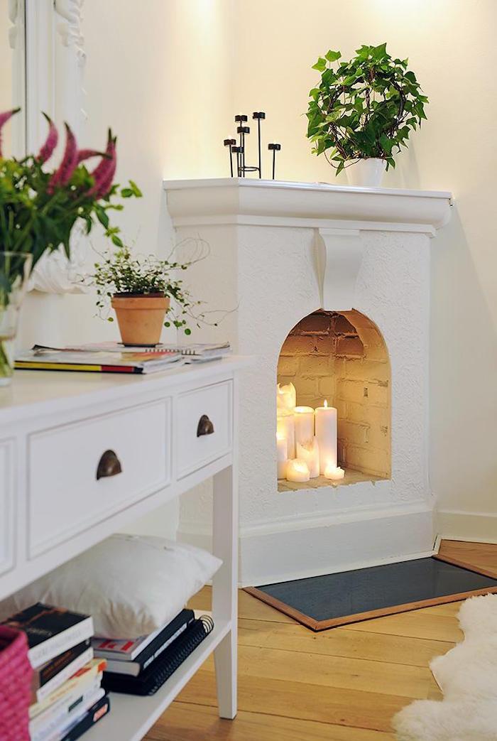 ancienne cheminée d'angle blanche fermée avec lot de bougies decoratives dans insert pour ambiance scandinave dans salon blanc sur parquet et plantes vertes