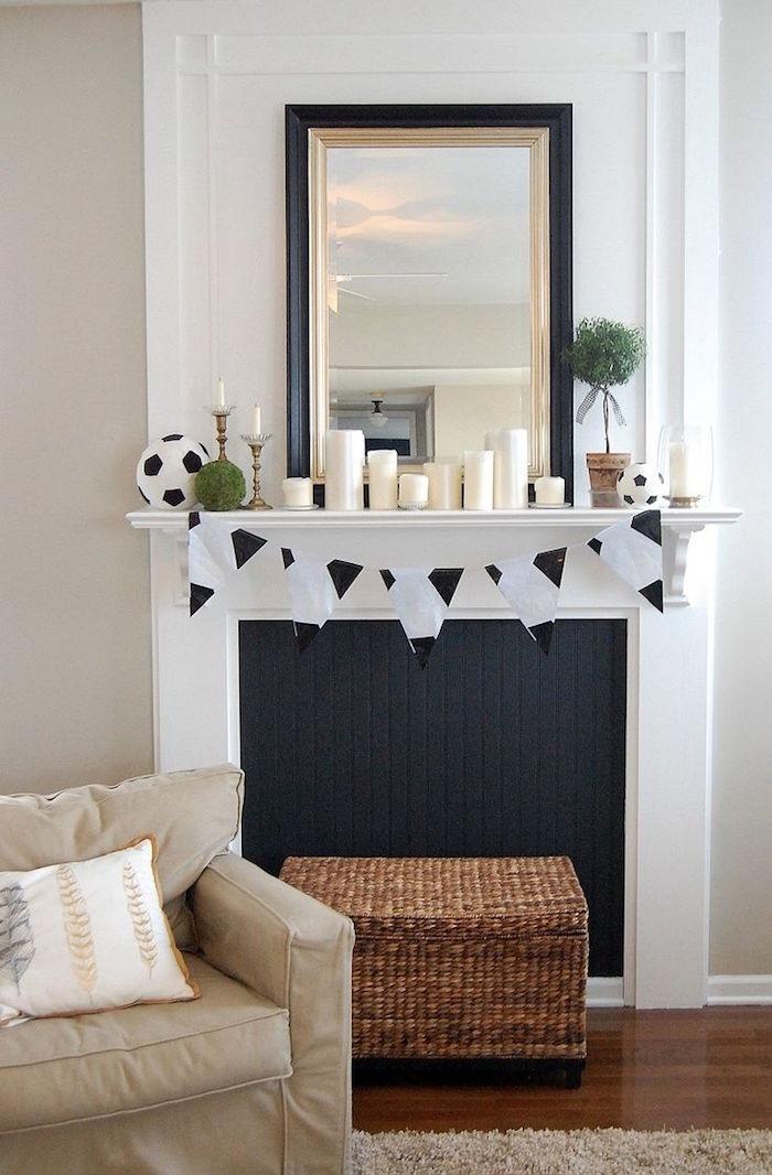 imitation cheminée blanche avec faux foyer noir dans salon au mur blanc et sol parquet ciré, bougies déco différentes tailles et coffre pouf en rotin