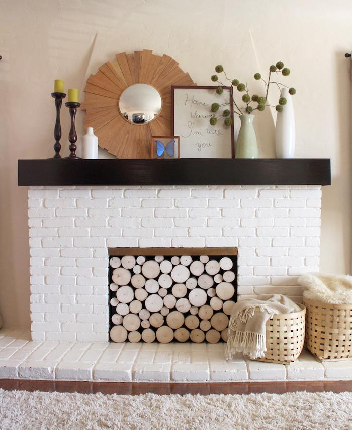 faux manteau cheminée décoratif en briques blanches aec buches bois dans foyer moquette beige sur le sol et objets deco style ambiance scandinave