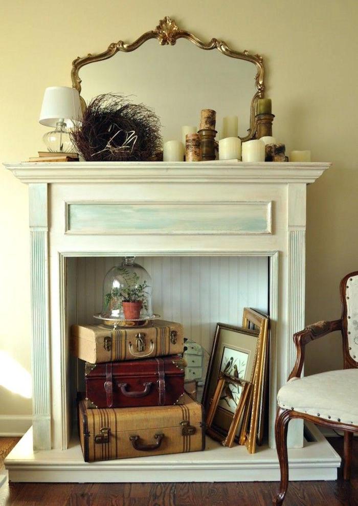 meuble imitation cheminée en bois nblanc bleu patine pour décoration retro avec vieilles valises vintage cadres et bougies