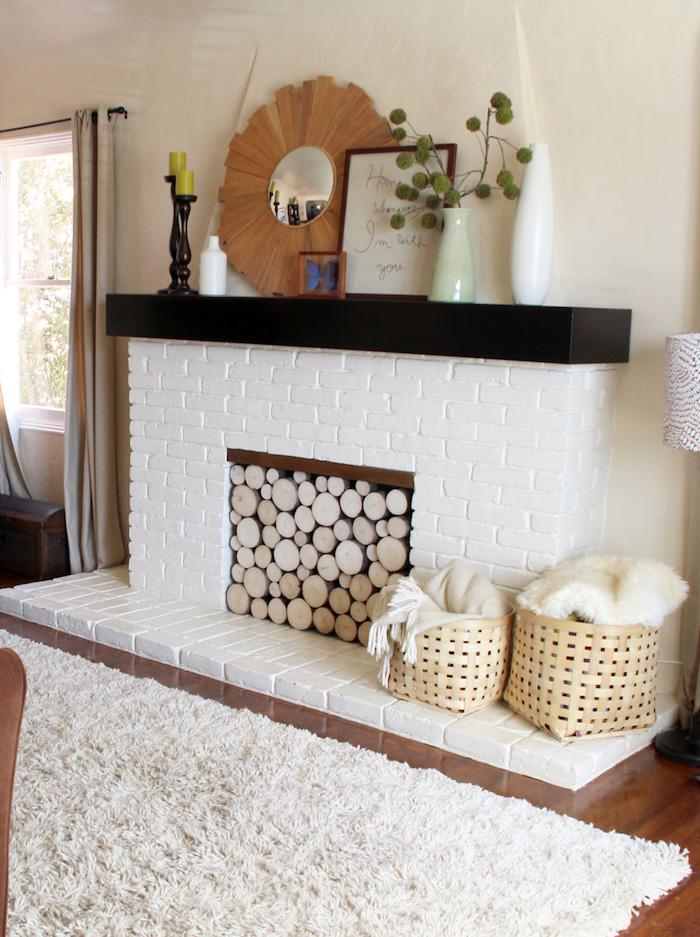 manteau cheminée décorative en briques blanche avec support noir dans salon déco scandinave sur sol parquet avec moquette beige panier en rotin et buches de décoration dans foyer