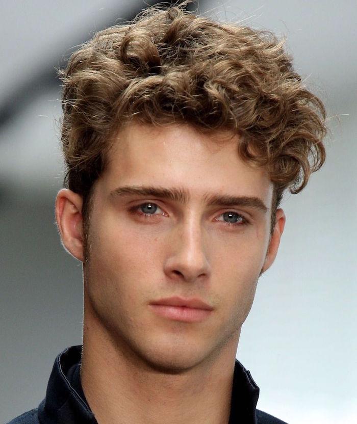 jeune homme avec cheveux ondulés mi long et coupe dégradé avec yeux bleus