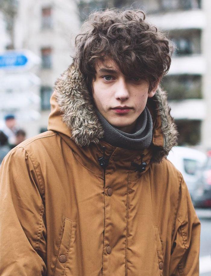 jeune garçon brun avec cheveux bouclés mi long tombant sur le front et blouson marron hiver