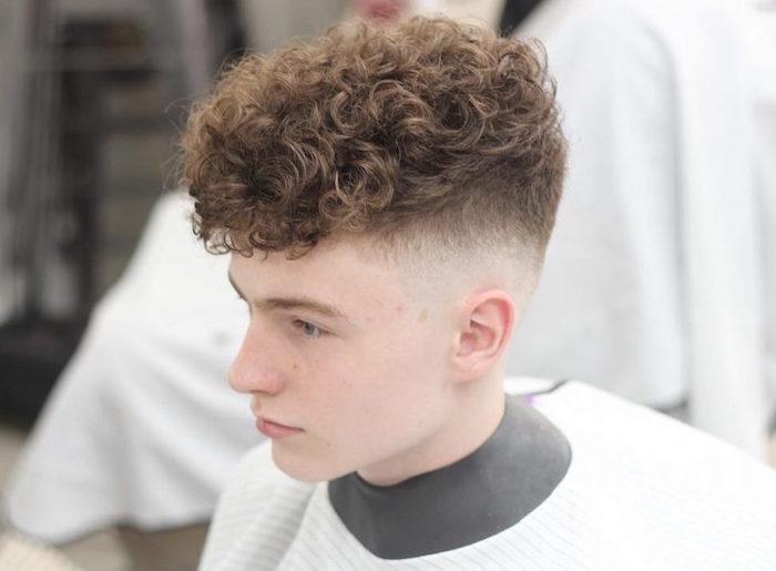 jeune blanc blond avec coiffure tendance homme avec coté tres court dégradé et plus long dessus