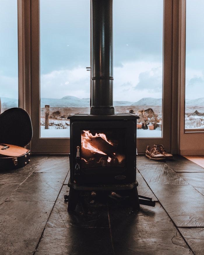 choisir une poêle à bois pour chauffer un salon rustique, idée petite cheminée design noire sur un carrelage en dalles de pierre