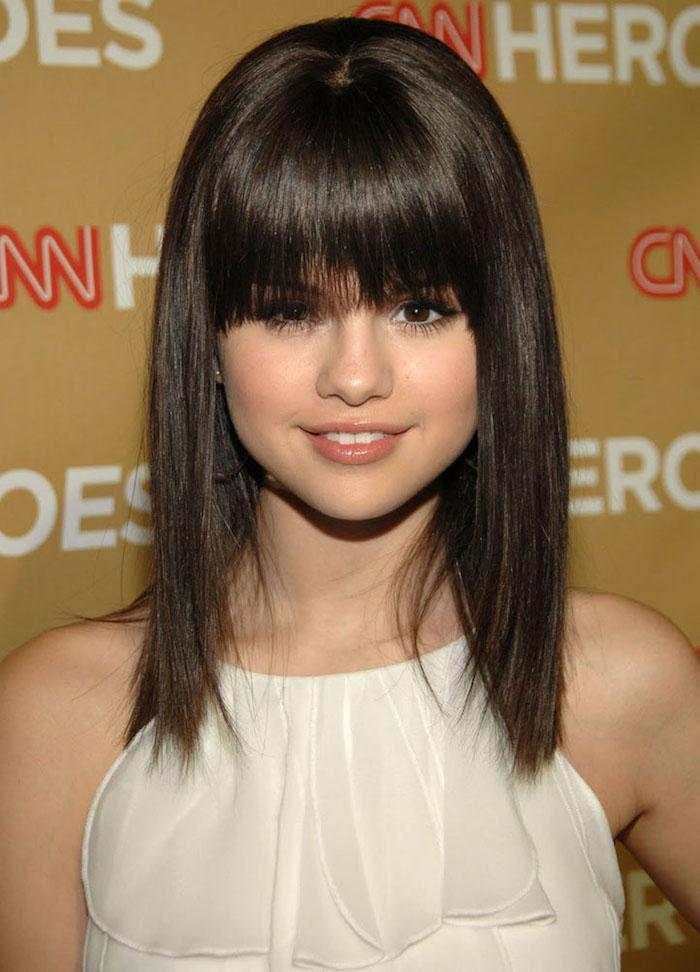 coiffure jeune fille brune carré long lisse aux épaules avec frange sur les yeux et robe de gala blanc cassé