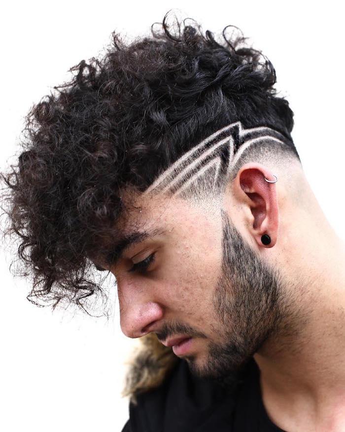 coupe tendance homme brun avec dessin tondeuse coté et cheveux bouclés sur le dessus tombant vers l'avant