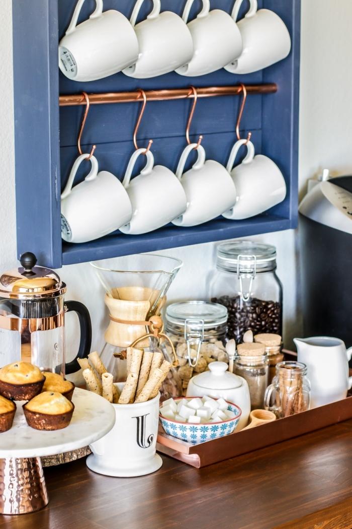 une étagère murale avec barres en cuivre et des crochets qui sert d'un support pour les tasses à café, coin café aménagé sur un bout du comptoir en bois