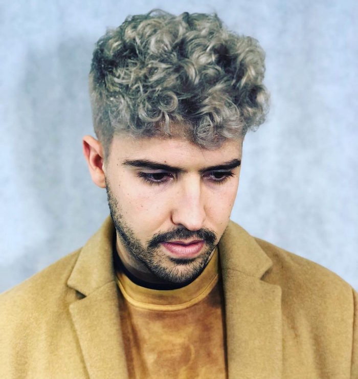 homme hipster cheveux bouclés avec coiffure tendance court sur le coté avec coloration blond gris et veste vintage beige