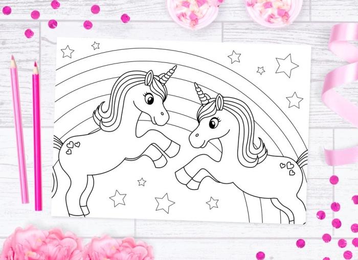 un coloriage de licorne à imprimée avec deux petites licorne jouant ensemble devant un arc-en-ciel