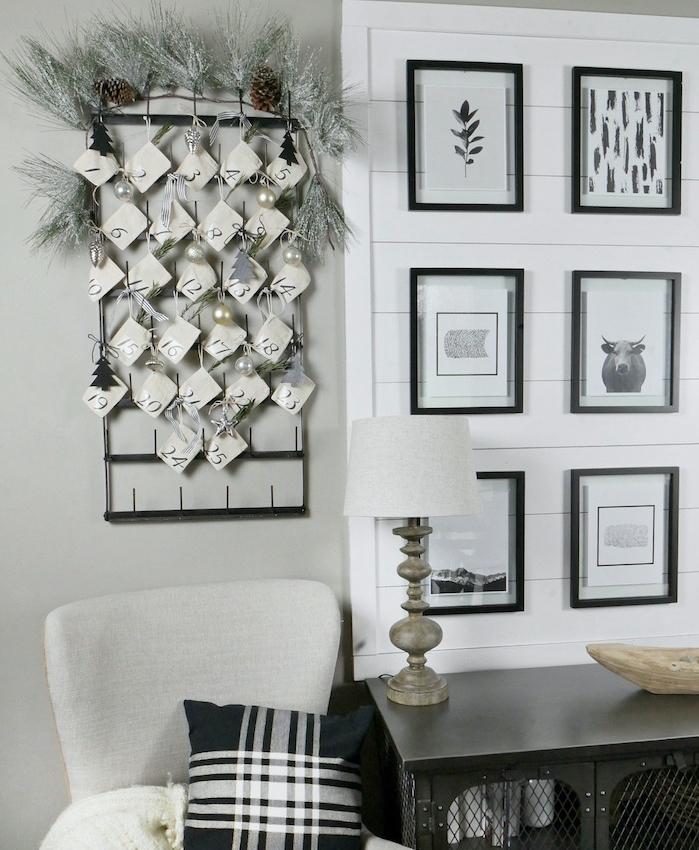 calendrier de l avent mural, petits sachets blanc avec surprises et décoration de branches de pin, boules de noel sur grillage noir, deco noir et blanc salon