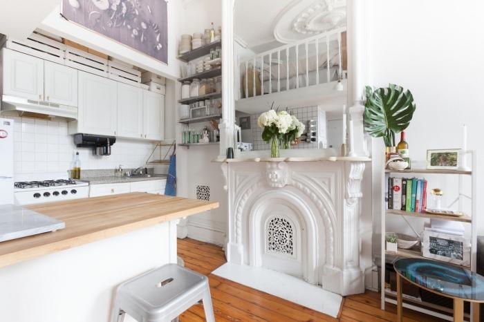 solutions de rangement astucieux pour aménager une petite cuisine fonctionnelle, cuisine blanche équipée d'un îlot centra bois et blanc et de placards, disposant aussi d'une multitude de petites étagères ouvertes et d'une fausse cheminée décorative originale
