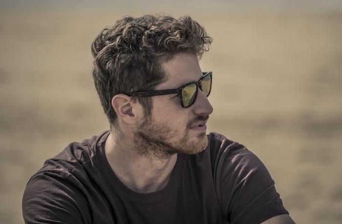 coiffure cheveux frisés homme mi long avec dégradé et barbe courte avec tee shirt marron et lunettes de soleil