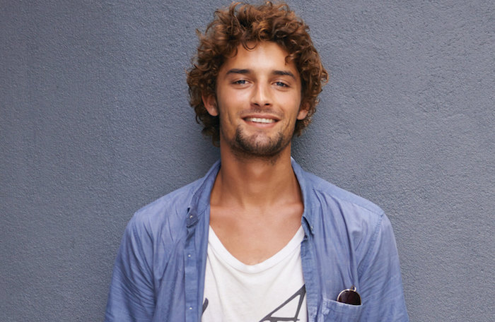 photo cheveux bouclés homme chatain marron mi long avec chemise bleue sur tee shirt blanc