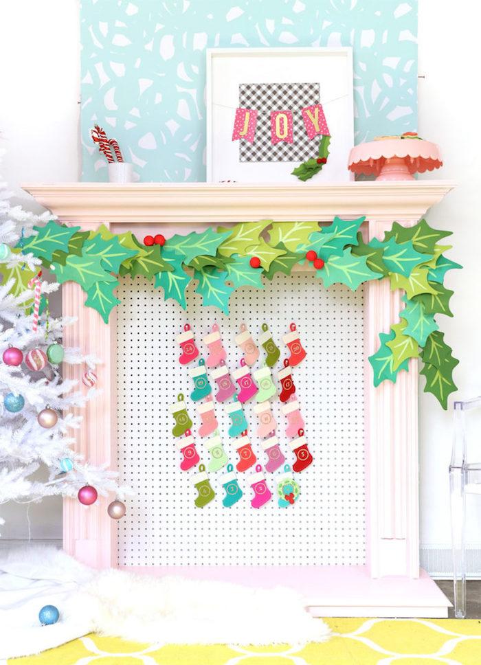 petites chaussettes de noel accrochées sur panneau perforé face d'une cheminée décorative de noel, guirlande de feuilles de houx