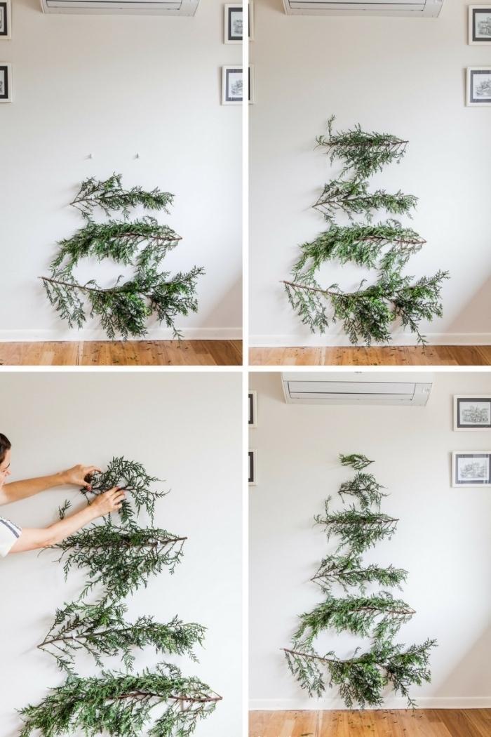 decoration de noel fait main de style minimaliste et naturel, des branches vertes naturelles accrochées au mur pour former un sapin de noel
